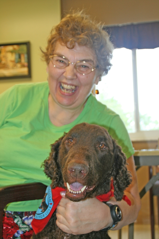 Leilah, a Curly Coated Retriever, interacts with resident.